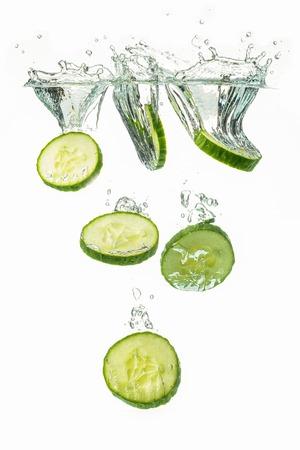 Sliced cucumber splashing water isolated on white background. Vertical photo. Skin moisturizing cosmetics concept Stock Photo