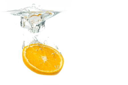 Orange fruit slice in water splash on white background