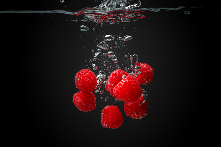 Raspberries falling into crystal clear water. Isolated on black background Reklamní fotografie