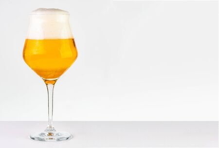Glass of cold golden beer isolated on a white background