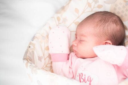Sleeping newborn baby. Cute little girl 4 days old. Adorable lying on side with gloves.