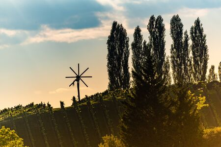 Wiew at wind mill on vineyard of south styrian wine route in Austria in sunset. Glanz an der Weinstrasse.