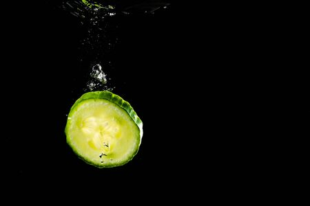 Sliced cucumber splashing water isolated on black background. Health and cosmetics concept. Underwater Stock fotó