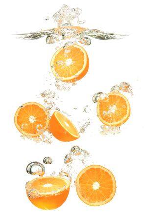 Oranges fruits dropped into water splash on white background. Healthy food