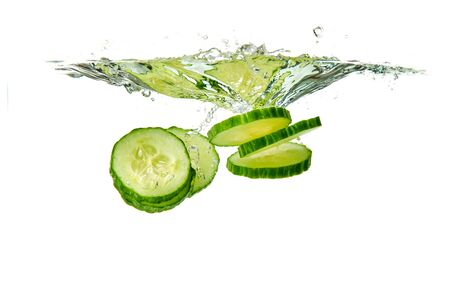 Sliced cucumber splashing water isolated on white background. Vertical photo. Skin moisturizing cosmetics concept Stock fotó