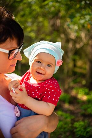 An emotional picture of 1 year old baby and her mother feeling happy together in the sunny summer forest. Reklamní fotografie - 133222611