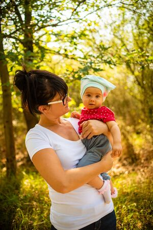 An emotional picture of 1 year old baby and her mother feeling happy together in the sunny summer forest. Reklamní fotografie