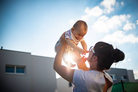 An emotional picture of 1 year old baby and her mother holding her up in the air against blue sky and bright sun. Motherhood concept