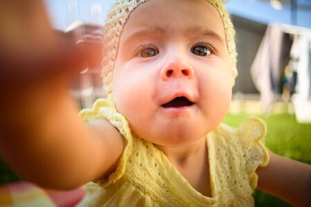 Cute baby girl in yellow reaching camera in sunny day outdoors. Conceptual.