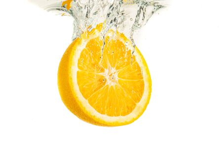 Orange half splashing into water and sinking isolated on white background. Citrus drink concept. Healthy food Stok Fotoğraf