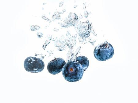 Mirtilli che spruzzano in acqua isolati su priorità bassa bianca. Fotografia del prodotto, concetto antiossidante. Archivio Fotografico