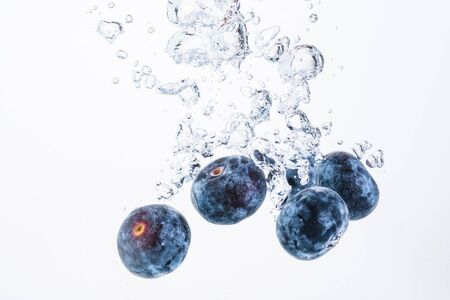 Blueberries splashing in water isolated on white background. Product photography, antioxidant concept.