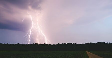 Lightning bolt at night over rural area. Agriculture fields.