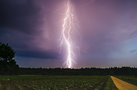 Lightning bolt at night over rural area. Agriculture fields. Stock Photo