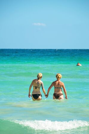 Alcudia, Spain 14.09.2011 - A couple holding hands in the sea. Two womans couple enjoying summer sun on vacation. Mallorca island famous tourist destination. 報道画像