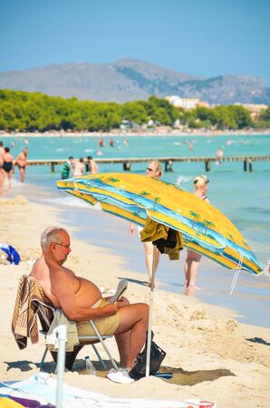 Alcudia, Spain 14.09.2011 - Older overweight man reading a newspaper at sandy beach under umbrella. People sunbathing at Playa de Muro. Mallorca island famous tourist destination