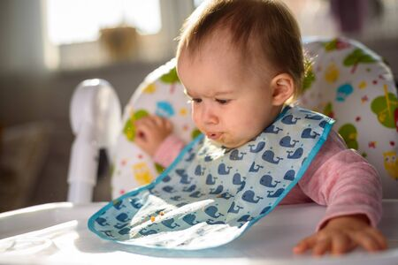 Baby not liking the food and spits it out. Sitting in a high chair in bright living room. 6- 12 months old. Feeding baby concept Stock Photo