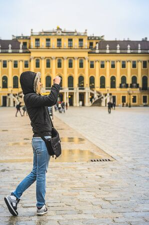 Vienna, Austria 02.11.2013 Young woman at Schonbrunn palace square in Vienna making photos, Austria. rainy day in tourist spot. 報道画像