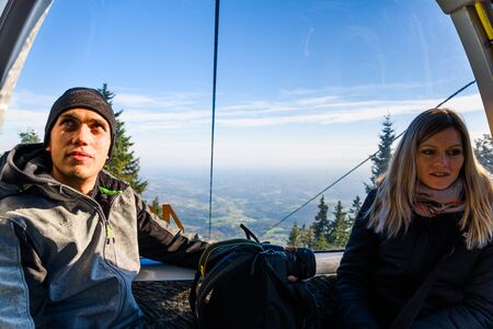 A couple in cable cart on the way to Schockl mountain. Famous travel destination