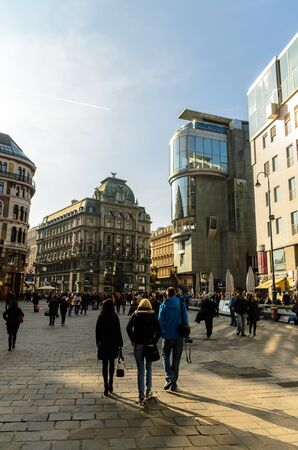 Crowd of people at the Stephansplatz in Vienna, Austria. View of famous landmark with many shops, restaurants, bars and modern buildings