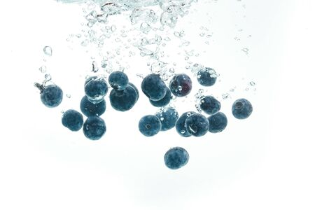 Blueberries falling into water on white background