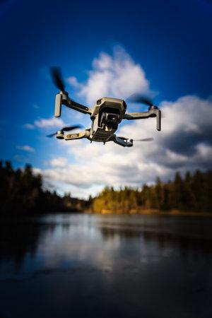 Graz, Austria - December 29 2019. DJI Mavic Mini drone flying in the countryside above frozen lake on sunny winter day