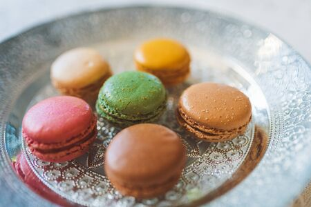 Traditional french colorful macarons on plate on table