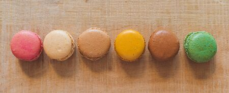Traditional french colorful macarons in a row on table