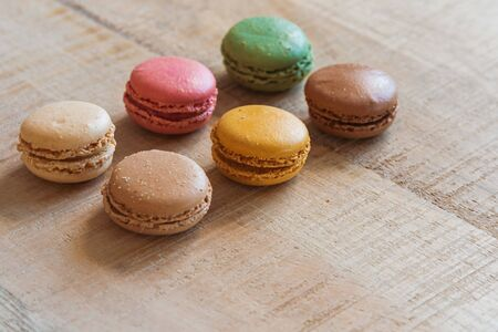 Traditional french colorful macarons in a row on table. Colorful cookies.