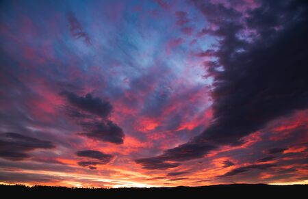 Beautiful dramatic sunset over Styrian land in Austria. Colorful winter evening on countryside. Background