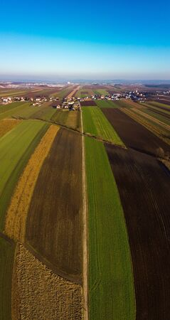 Aerial panorama view of countryside on sunny winter day in Styria , Austria. Route in beautiful nature landscape with sun, blue sky, and green fields. Background Reklamní fotografie