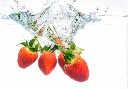Strawberries falling into water causing bubbles all around it. Healthy food concept. Underwater, splash photography.