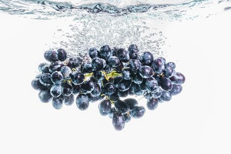 Bunch of red grapes splashing into crystal clear water on withe background. Healthy food Stock Photo
