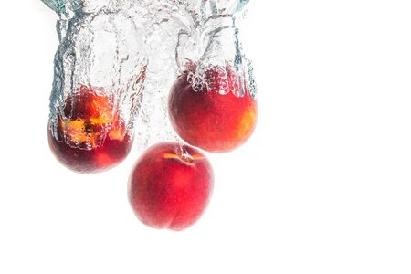 Nectarine fruits splashing into water and sinking with air bubbles isolated on white background. Copy space