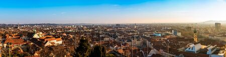 Graz, Styria Austria - Wide panorama of Graz City, City rooftops, Mur river and city center, Schlossberg hill and clock tower Sun in winter, blue sky. Travel destination.