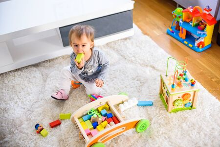 Portrait of one year old baby girl indoors playing on the carpet in bright room
