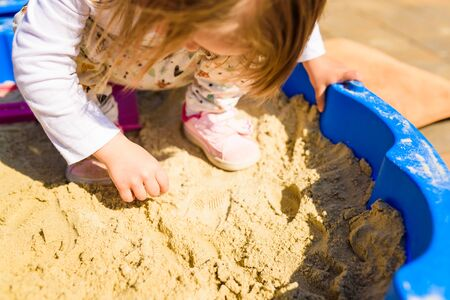 Baby girl playing in a sandbox outdoors in sunny day. Child in blue sandbox in summer.