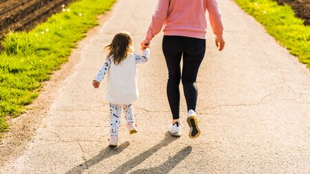 Mother and child walking on countryside road between agricultural fields towards forest in Austrian vilage durring sunset. Active family life without stress. Foto de archivo