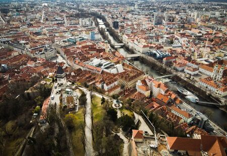 Aerial view from Graz hill Schlossberg in Austria, cityscape with house roofs, mur river and all famous landscapes of tourist city. Drone shoot from above.