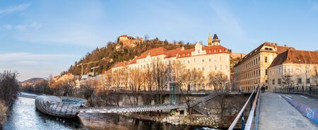 Graz, Styria Austria - 20.01.2019: Panorama view at Mur river, Murinsel on bridge, Schlossberg hill with fortress and clock-tower Uhrturm. Travel destination. Stock Photo