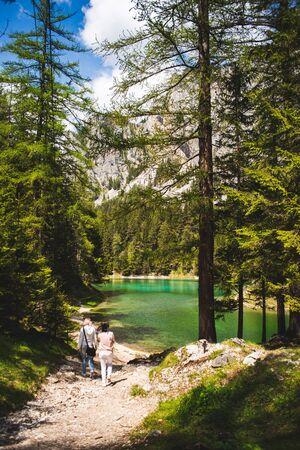 Green Lake, Styria, - Austria.16.05.2017: Gruner See place to visit, tourist destination. Vertical photo two young girls walking towards lake