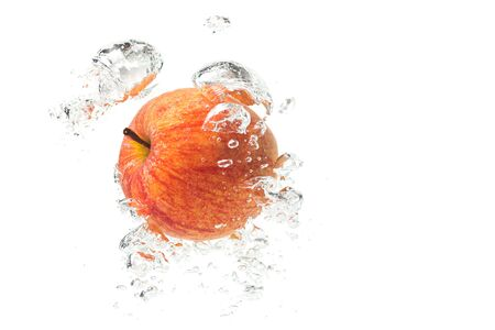 Apple falls under water with a splash. With lots of air bubbles