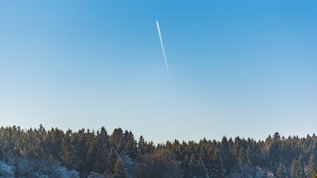 Landscape of forest against blue sky with plane trail on sunny frosty morning. Nature background Stock Photo