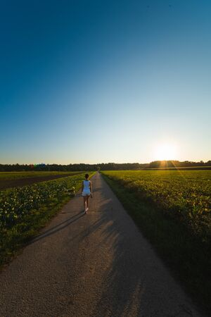 Girl is walking with a beagle dog on a leash in the sunset to the forest in rural area. Vertical photo