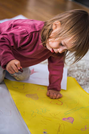 Two year old drawing on papper with wax crayons, sitting on floor indoors. Education and creativity development concept.