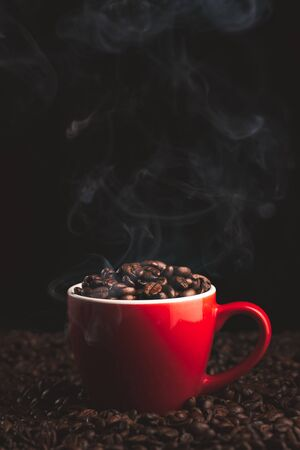 Red Cup with smoking and steaming coffee beans on table covered with coffee beans.Coffe themed background