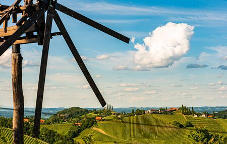 Vineyards famous Austria destination wine street in south Styria in summer. View at windmill on grape hill. Border with Slovenia. Wine country in summer. Tourist destination. Green hills and crops Stok Fotoğraf