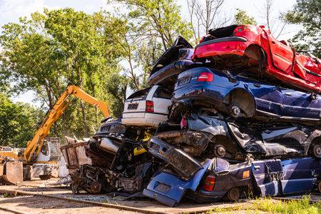 Graz, Austria - 24.06.2020 - Cars piled on top of each other in junkyard Redakční