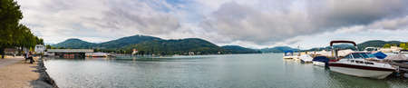 Klagenfurt, Austria - Great lake Klagenfurt am Worthersee. Many boats are anchored. Summer holiday resort of many European tourists. Crystal blue water.