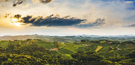 Gorgeous sunset over beautiful green vineyards. Aerial panorama sunset over Austrian grape hills in summer. Wine culture in south styria, tuscany like tourist famous spot.